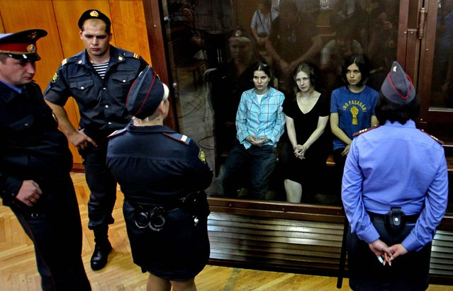 Yekaterina Samutsevich, Maria Alekhina and Nadezhda Tolokonnikova sit behind a glass wall at the court in Moscow. (Photo by Mikhail Metzel/Associated Press)