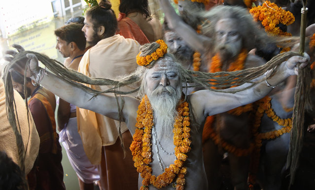 A naked Hindu holy man arrives to bath in the Godavari River during Kumbh Mela, or Pitcher Festival, at Trimbakeshwar in Nasik, India, Saturday, August 29, 2015. (Photo by Rajanish Kakade/AP Photo)