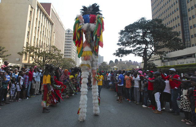 In this picture taken Saturday, September 9, 2017, traditional Zimbabwean nyau dancers prepare to perform on the streets of Harare during the Harare International Carnival in the capital. (Photo by Tsvangirayi Mukwazhi/AP Photo)