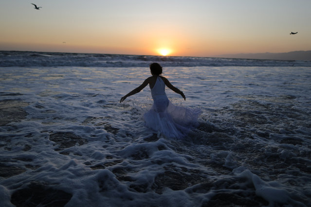 A girl runs into the Pacific Ocean at a Tashlich ceremony, a Rosh Hashanah ritual to symbolically cast away sins, during the Nashuva Spiritual Community Jewish New Year celebration on Venice Beach in Los Angeles, California, United States September 21, 2017. (Photo by Lucy Nicholson/Reuters)