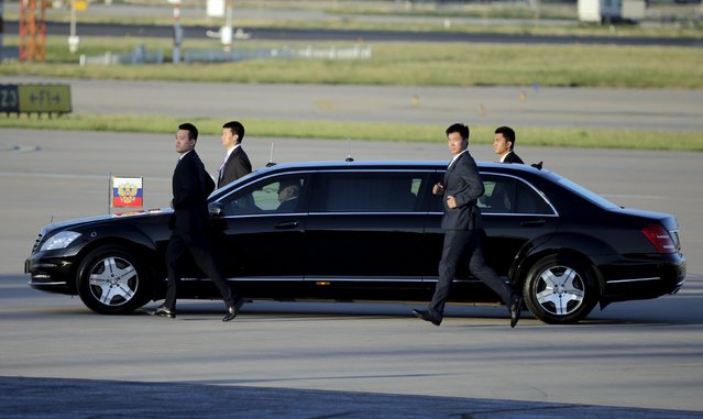 Security personnel run following a car carrying Russian President Vladimir Putin after arriving at Beijing International Airport, China, September 2, 2015, ahead of attending the commemoration of the 70th anniversary of the end of World War Two. (Photo by Jason Lee/Reuters)