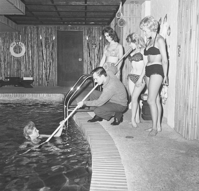 Playing at having fun, Hugh Hefner, center, rescues one of the swimmers in the indoor pool of his $400,000 apartment, June 20, 1961, Chicago, Ill. The wealthy young publisher doesnt do much swimming in the pool himself. Surrounded by everything for a playboys dream life, Hefner doesnt fit into the image his magazine has created. The women are unidentified. (Photo by Edward Kitch/AP Photo)