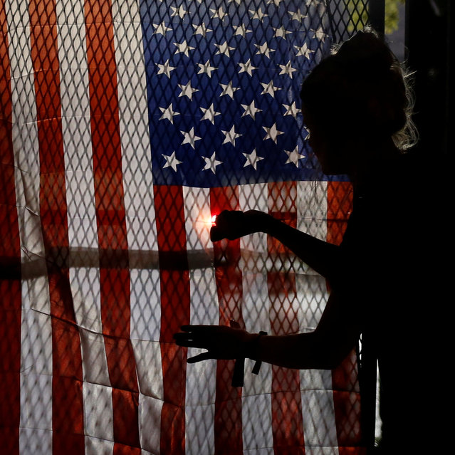 An activist lights the U.S. flag aflame along the perimeter fence of the 2016 Democratic National Convention in Philadelphia, Pennsylvania on July 28, 2016. (Photo by Adrees Latif/Reuters)