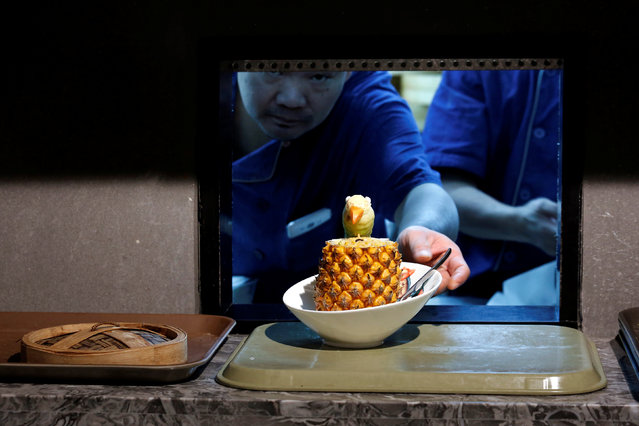 A cook delivers a fried rice with pineapple from the kitchen at Dim Sum Icon restaurant in Hong Kong, China July 25, 2016. (Photo by Bobby Yip/Reuters)