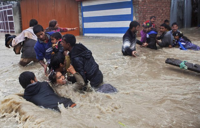 Kashmiri residents struggle to withstand sudden and strong water currents while wading through floodwaters in their efforts to move to safer places in Srinagar, India, Thursday, September 4, 2014. At least 100 villages across the Kashmir valley were flooded by overflowing lakes and rivers, in the worst flooding in 22 years caused by heavy rains. (Photo by Dar Yasin/AP Photo)