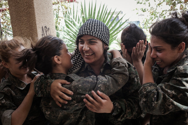 Young YPJ recruits cry and embrace a fellow soldier who they thought had been sent to the frontline and were surprised to see her return, near Derek City, Syria. The YPJ schedule is demanding and requires discipline – new soldiers in training get about 6 hours of sleep a night and wake up at 4 AM to begin exercising; afterwards, their day consists of a full schedule of drills and classroom lessons. Before joining the YPJ many of the girls had never participated in physical activity or sports before. (Photo by Erin Trieb/NBC News)