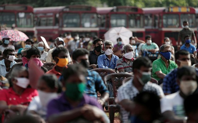 People who couldn't return to their hometowns due to a lockdown amidst concerns about the spread of coronavirus disease (COVID-19) wait to travel to their villages using special transport organised by the government, at a public ground in Colombo, Sri Lanka, May 2, 2020. (Photo by Dinuka Liyanawatte/Reuters)