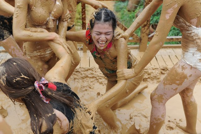 This photo taken on September 10, 2014 shows women playing with mud in a tourist area of Zhangjiajie, central China's Hunan province. The Asia-Pacific region, led by China, will be the main force driving world tourism in the next 10 years, according to a consultancy survey forecast. (Photo by AFP Photo)