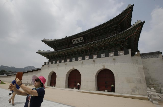 A woman takes a selfie near the Gwanghwamun, the main gate of the 14th-century Gyeongbok Palace and also one of South Korea's well known landmarks in Seoul, South Korea, Tuesday, July 28, 2015. (Photo by Lee Jin-man/AP Photo)