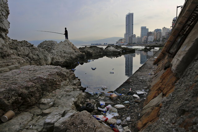 "In this Wednesday, November 14, 2018 photo, a man casts his fishing pole in the Mediterranean Sea as trash are seen on a rocky coastal area along the Beirut coastline, Lebanon. Fisherman Ahmad Obeitri, who has been a fixture at Lebanon's corniche for the past 30 years, says the trash is killing off what's left of marine life. ""These days if a fish comes our way it will only find nylon bags, garbage and sewage to feed on"", he said, lamenting the people who eat and drink as they walk on the corniche and then toss their cans, tins and other containers in the sea. ""You can open a cafe under water and invite your friends"", he adds sarcastically. (Photo by Hassan Ammar/AP Photo)"