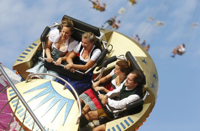 Visitors enjoy a firground ride during the opening day of the 181st Oktoberfest in Munich September 20, 2014. Millions of beer drinkers from around the world will come to the Bavarian capital over the next two weeks for the Oktoberfest, which starts today and runs until October 5. (Photo by Michael Dalder/Reuters)