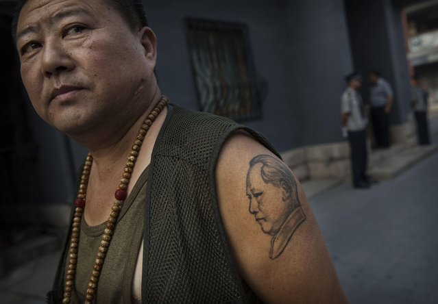 A Chinese collector has a tattoo of the late Mao Zedong on his arm as he waits outside a sale and auction of memorabilia dedicated to him on September 19, 2014 in Beijing, China. (Photo by Kevin Frayer/Getty Images)