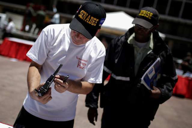 An official holds up a pistol during an exercise to disable seized weapons in Caracas, Venezuela August 17, 2016. (Photo by Marco Bello/Reuters)