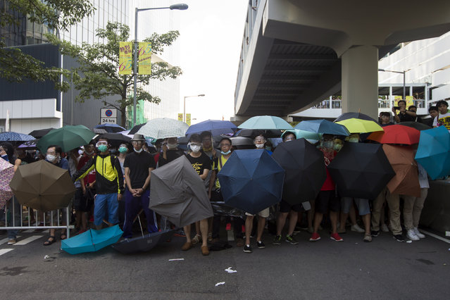 Protesters carry umbrellas to try to protect themselves from being pepper-sprayed during a confrontation with the police in Hong Kong September 27, 2014. (Photo by Tyrone Siu/Reuters)