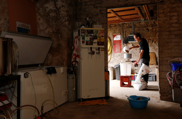 Axel Henrard, psychologist and President of the Belgian Homebrewers association, mills malt in a former barn of his house as he starts making his own beer in Attert, Belgium, August 11, 2016. (Photo by Francois Lenoir/Reuters)