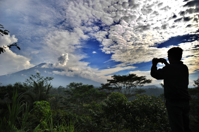 A man takes a photo as a puff of smoke comes from Mount Agung volcano, taken from the Rendang sub-district in Karangasem Regency on Indonesia's resort island of Bali on November 23, 2017. Thousands living in the shadow of the rumbling volcano on Indonesia's resort island of Bali fled on November 22 as fears grow that it could erupt for the first time in more than 50 years. (Photo by Sonny Tumbelaka/AFP Photo)