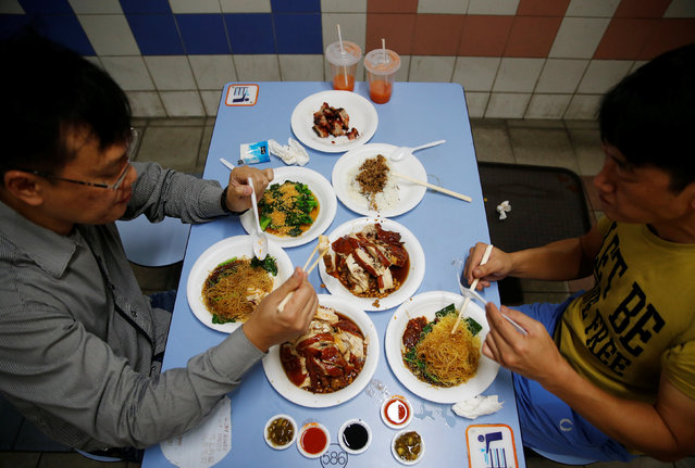 Patrons eat Michelin-starred soya sauce chicken noodles at Chinatown food centre in Singapore July 22, 2016. Singapore's beloved hawker industry faces an uncertain future with a wave of chef retirements imminent, raising questions about who will cook the city state's signature street-food delights. There are over 100 hawker centres and 6,000 stalls in Singapore, run mainly by ageing chefs, with people from all sections of society attracted to the tasty multi-ethnic meals that cost as little as S$2.80 ($2). (Photo by Edgar Su/Reuters)