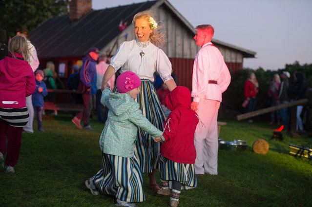 A woman wearing an Estonian tradionnal costume dance with children during the Night of Ancient Bonfires, a centuries-old maritime tradition also focused now on environmental awareness, on August 27, 2016 in Tallin. Hundreds of bonfires dotted the Baltic Sea coast of Estonia on the night of August 28, 2016, a centuries-old maritime tradition to guide seafarers now celebrated with a tech-savvy environmental twist. Summer revellers from as far as Finland, Sweden, Latvia and Russia also signed up to be part of the event on the interactive Ancient Bonfires website set up by Mairold Vaik. (Photo by Raigo Pajula/AFP Photo)