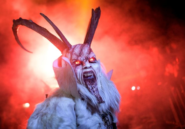 "A participant dressed as a ""Krampus"" creature walks during ""The Hike of the Krampus of Three Lands"" in Podkoren, Slovenia on November 24, 2017. (Photo by Jure Makovec/AFP Photo)"