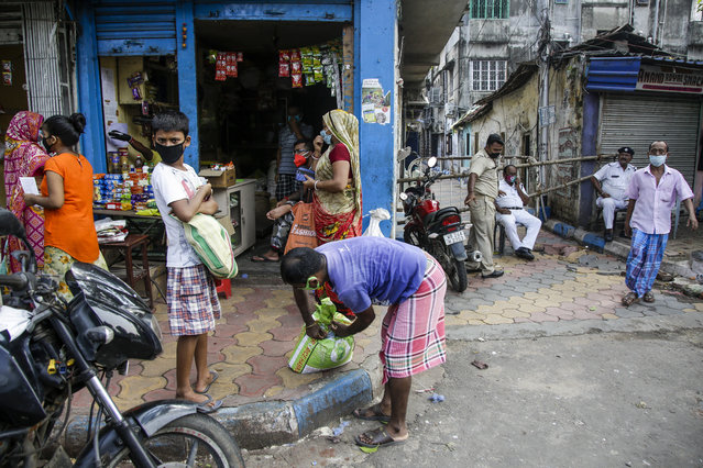 People buy essentials from a grocery shop just outside a containment zone barricaded, right, to prevent the spread of the coronavirus in Kolkata, India, Tuesday, July 14, 2020. (Photo by Bikas Das/AP Photo)