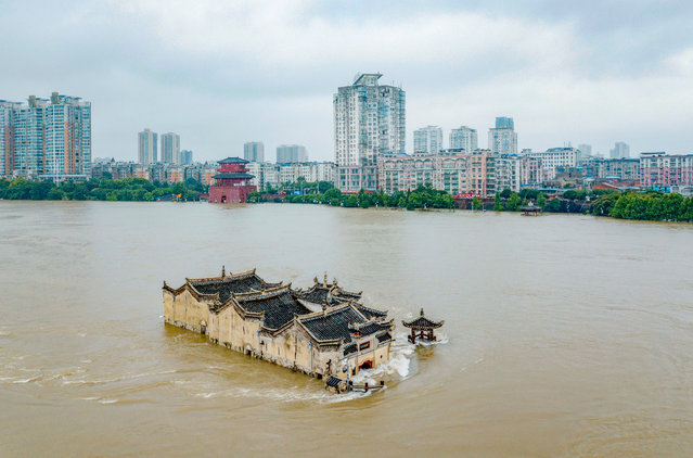 This photo taken on July 19, 2020 shows the Guanyinge temple, a 700-year old temple built on a rock, in the swollen Yangtze River in Wuhan in China's central Hubei province. Heavy rains since June have left at least 141 people dead and missing, forced nearly 15 million people to be evacuated from their homes in July alone, and caused billions of dollars in economic losses, according to the government. (Photo by AFP Photo/China Stringer Network)