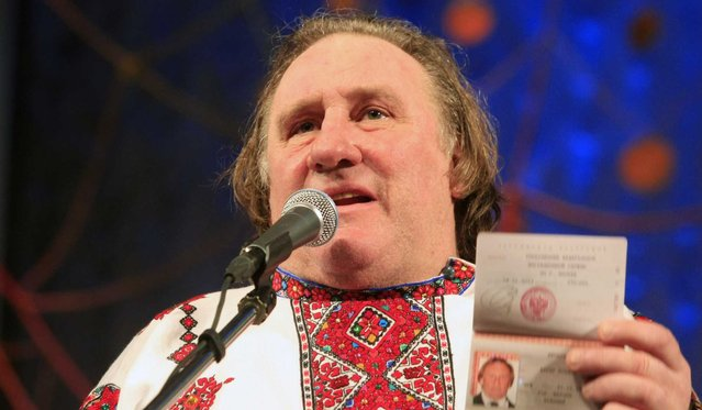 Actor Gerard Depardieu poses with his new Russian passport on a theatre stage, wearing a traditional folk outfit, after he arrived in the city of Saransk, 700 kilometres east of Moscow, January 7, 2013. (Photo by Mordovmedia.ru/Associated Press)