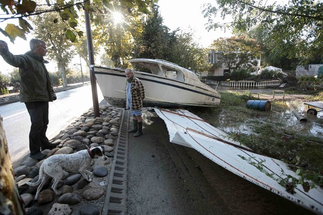 Men stand near a boat which sits on a damaged fence in a garden after flooding caused by torrential rain in Biot, France, October 4, 2015. (Photo by Eric Gaillard/Reuters)