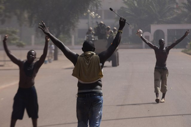 Anti-government protesters confront the military in front of the parliament building in Ouagadougou, capital of Burkina Faso, October 30, 2014. (Photo by Joe Penney/Reuters)