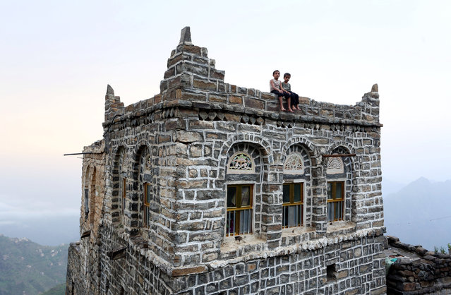 Boys sit on an edge of the roof of their house in the mountains, in the Jafariya district of the western province of Raymah, Yemen May 31, 2016. (Photo by Abduljabbar Zeyad/Reuters)