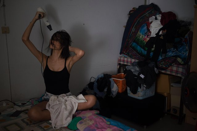 "Kritchaya ""Lolita"" Boonhor dries her hairs in her room to meet her friends for the evening, in Bangkok, Thailand, 27 November 2017. (Photo by Lola Levan/EPA/EFE)"