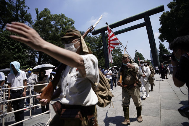 Visitors in Japanese Imperial army and navy uniforms enter Yasukuni Shrine, which honors Japan's war dead, Saturday, August 15, 2020, in Tokyo. Japan marked the 75th anniversary of the end of World War II. (Photo by Eugene Hoshiko/AP Photo)
