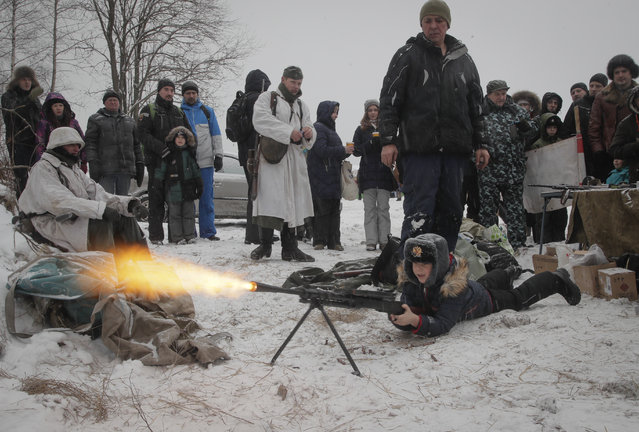 A boy shoots a World War II machine gun armed with blanks at an weapon exhibition during a military show near Kirovsk, about 30 kilometers (19 miles) east of St. Petersburg, Russia, Sunday, January 21, 2018. (Photo by Dmitri Lovetsky/AP Photo)