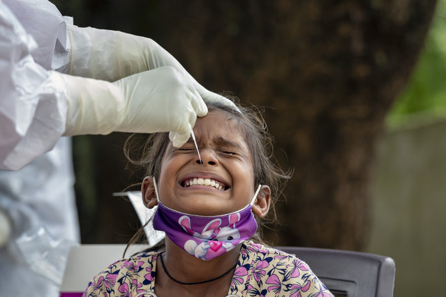 An Indian girl cries as a medical worker collect her swab sample for COVID-19 test at a rural health center in Bagli, outskirts of Dharmsala, India, Monday, September 7, 2020. India's coronavirus cases are now the second-highest in the world and only behind the United States. (Photo by Ashwini Bhatia/AP Photo)