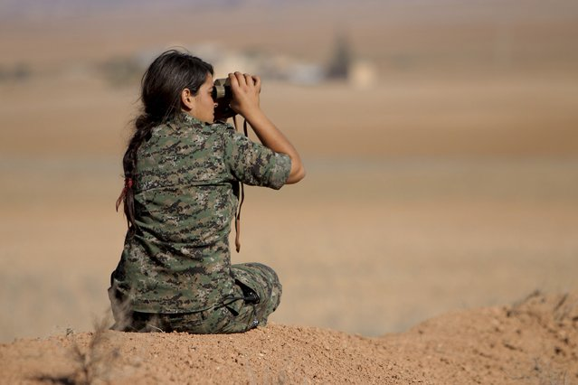 A female fighter of the Kurdish People's Protection Units (YPG) uses a pair of binoculars as she looks towards areas controlled by Islamic State fighters in the southern countryside of Ras al-Ain November 9, 2014. (Photo by Rodi Said/Reuters)