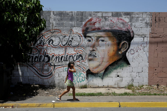 A girl walks past a mural depicting Venezuela's late President Hugo Chavez in Villa Rosa, near Porlamar, Venezuela September 16, 2016. (Photo by Marco Bello/Reuters)