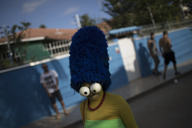 """A reveler poses for a picture during the Perola da Guanabara street party at the Paqueta island in the Guanabara bay in Rio de Janeiro, Brazil, Saturday, February 3, 2018. Merrymakers take to the streets in hundreds of open-air """"bloco"""" parties ahead of Rio's over-the-top Carnival, the highlight of the year for many. (Photo by Leo Correa/AP Photo)"""