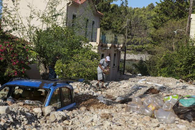 A man carries rocks following a storm at the village of Assos, on the Ionian island of Kefalonia, western Greece, Sunday, September 20, 2020. A powerful tropical-like storm named Ianos, battered parts of central Greece and some of the western Ionian islands, as emergency workers rescued more than 600 people. (Photo by Nikiforos Stamenis/AP Photo)