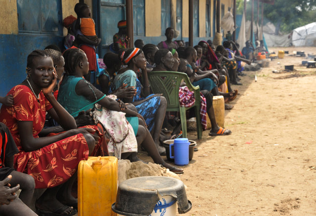 Internally displaced South Sudanese families sit outside a classroom as they shelter from flood water from the broken dykes on Nile river, in Duk padiet county of Jonglei State, in South Sudan on September 24, 2020. (Photo by Denis Dumo/Reuters)
