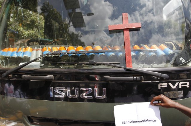 A wooden cross, symbolising people killed in a series of attacks, is placed by protesters on a police truck with teargas canisters behind the windscreen during the #OccupyHarambeeAve demonstration in Kenya's capital Nairobi November 25, 2014. (Photo by Thomas Mukoya/Reuters)