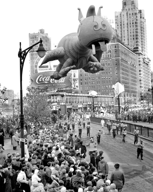 Thanksgiving Day is the day when Americans traditionally pause to count their blessing, have a good turkey dinner, and then start looking forward to Christmas. One of the annual highspots is Macy's Thanksgiving Day Parade, 1961. The floats, bands and balloons set out from Central Park West at 77th Street, swung down Broadway and ended up at Macy's., Big-headed dragon sails over Columbus Circle. (Photo by Gordon Rynders/NY Daily News Archive via Getty Images)