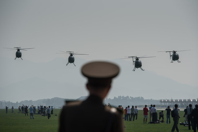 A North Korean soldier watches as Hughes MD-500 helicopters perform a fly-by during the first Wonsan Friendship Air Festival in Wonsan on September 24, 2016. (Photo by Ed Jones/AFP Photo)