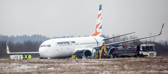 Teams of Czech and Polish experts are working to free a Czech Boeing 737 airplane from a muddy field at the airport in Katowice, Poland on Wednesday, March 13, 2013. The plane from the Czech Travel Service airline skidded late Tuesday and went some 20 meters (22 yards) off the Pyrzowice airport runway and ran into wet ground, where its front landing gear sank. None of the 176 passengers and six crew members was hurt. The airport remains closed and flights are redirected to nearby Krakow. (Photo by Artur Gierwatowski/AP Photo)
