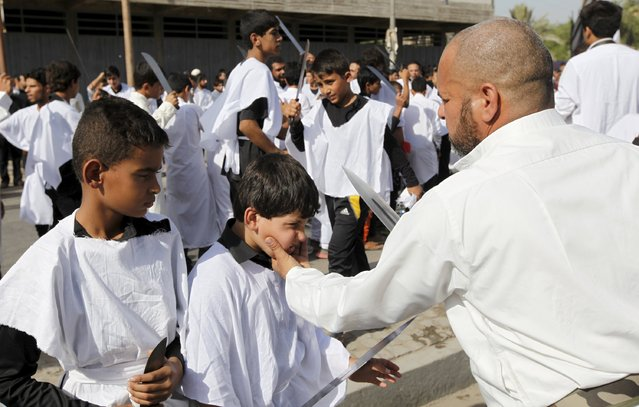A Shi'ite Muslim man prepares to gash a boy's head with a knife to commemorate Ashura in Baghdad, October 24, 2015. (Photo by Ahmed Saad/Reuters)