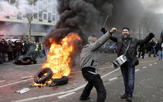 Employees of PSA Peugeot Citroen burn tyres during a demonstration in front of the Peugeot headquarters in Paris March 18, 2013 to protest against the closure of the PSA Aulnay automobile plant and the government's economic policy and industrial layoffs. (Photo by Jacky Naegelen/Reuters)