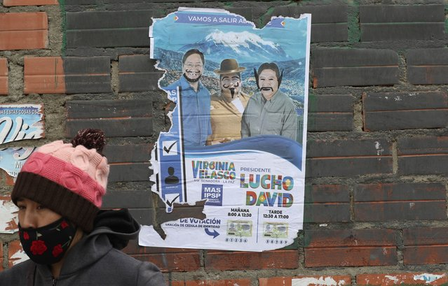 A child walks past a defaced election poster promoting presidential candidate Luis Arce representing the Movement Towards Socialism political party better known by its acronym MAS, in El Alto, Bolivia, Saturday, Octoner 17, 2020. Sunday's presidential election gives Bolivians a chance for a political reset as they struggle with the dramatic costs of the COVID-19 pandemic. (Photo by Martin Mejia/AP Photo)