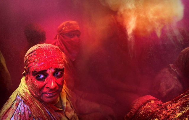 Hindu men from the village of Nangaon are covered in colored powder as they sit on the floor during prayers at the Ladali, or Radha temple, before the procession for the Lathmar Holi festival. (Photo by Kevin Frayer/Associated Press)