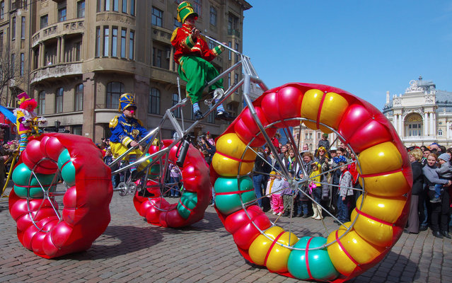 Alexey Kravtsov photographed this awesome tricycle with enormous balloon wheels being ridden, of course, by clowns. The spectacular sight was part of a parade taking place during the Humorina carnival, an annual festival of humour held in the Ukrainian city of Odessa on or around April Fool's Day, on April 1, 2013. (Photo by Alexey Kravtsov/AFP Photo)