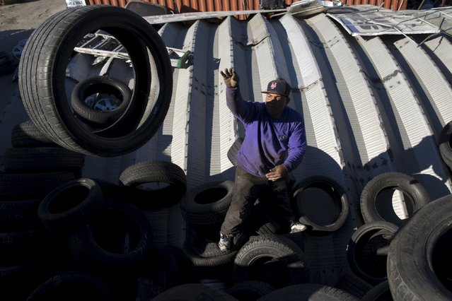 A worker reorganizes tires in the Willets Point area of Queens in New York October 26, 2015. (Photo by Andrew Kelly/Reuters)