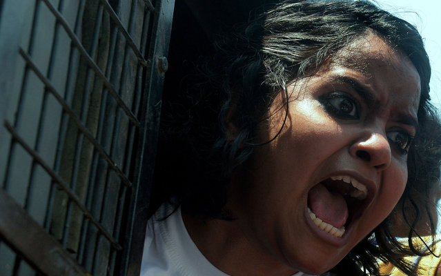 An activist from a leftist students' union shouts slogans against Gujarat Chief Minister Narendra Modi from a police van outside the venue of his meeting with business leaders in Kolkata, on April 9, 2013. Police arrested students and other protesters and tightened security around the venue. (Photo by Dibyangshu Sarkar/AFP Photo)