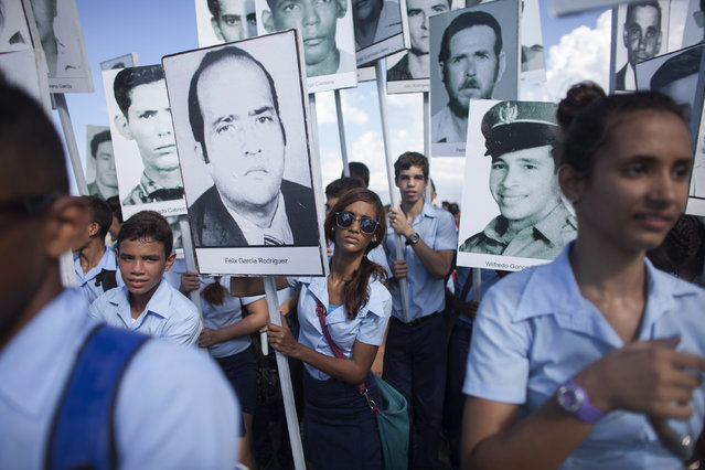 "Students hold photographs of victims from events such as the Bay of Pigs invasion and the bombing of a Cuban plane during a march in Havana ""For the Five and Against the Terrorism"", September 30, 2014. (Photo by Alexandre Meneghini/Reuters)"
